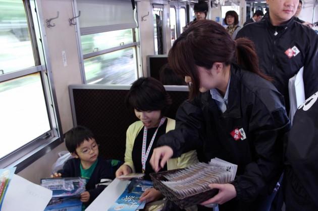 平川駅を過ぎて最初の振る舞い、出汁ガールがかつお煎餅を配ります